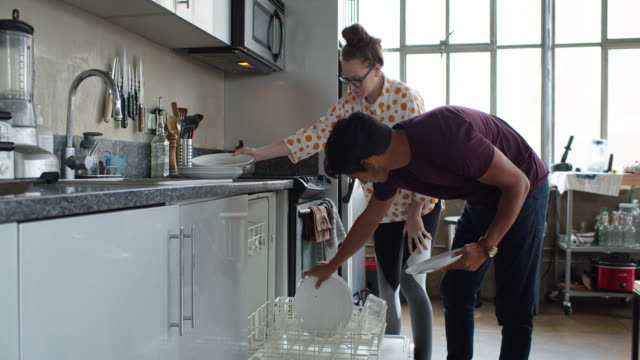vídeos de stock e filmes b-roll de slow motion shot of couple loading dishwasher - loft apartment