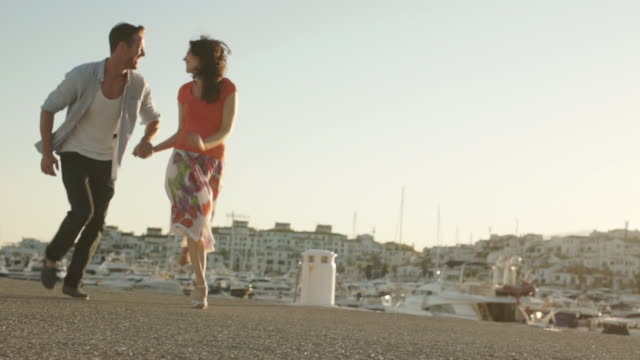 Slow motion shot of couple running by marina in sunset.