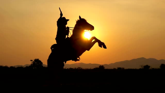 slow motion shot of cowboy riding horse and holding a gun at sunset - gallop animal gait stock videos & royalty-free footage