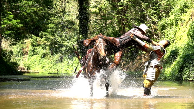 slow motion shot of cowboy riding horse and jumping to fight with ancient warrior - rivalry stock videos & royalty-free footage
