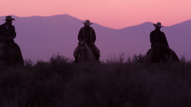stockvideo's en b-roll-footage met slow motion shot of cowboys riding towards the camera with pink sky in the background. - cowboyhoed