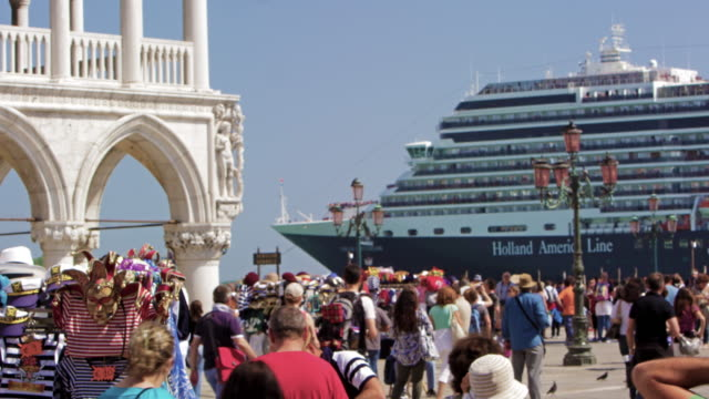 slow motion shot of cruise ship pulling up near piazza san marco - tourist stock-videos und b-roll-filmmaterial