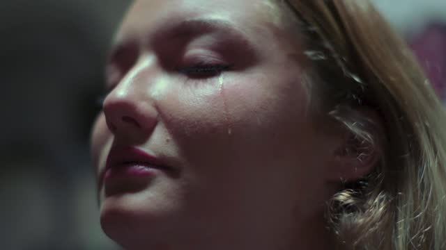 slow motion shot of crying woman with a tear falling down her cheek - young women stock videos & royalty-free footage