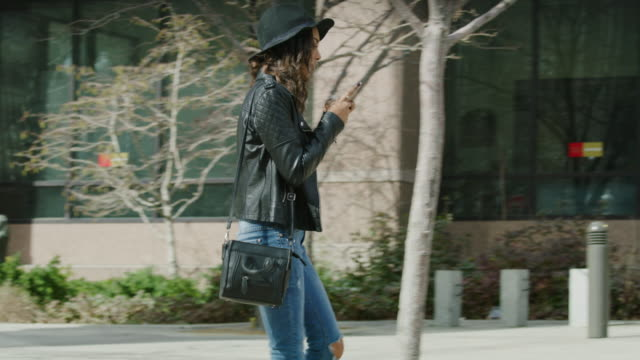 slow motion shot of distracted woman texting on cell phone walking into post on sidewalk / salt lake city, utah, united states - purse stock videos & royalty-free footage