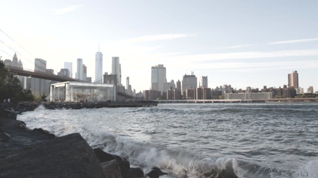 slow motion shot of east river waves crashing into shore in front of the new york city skyline - east river stock videos & royalty-free footage