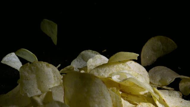 slow motion shot of falling potato chips - 塩味スナック点の映像素材/bロール