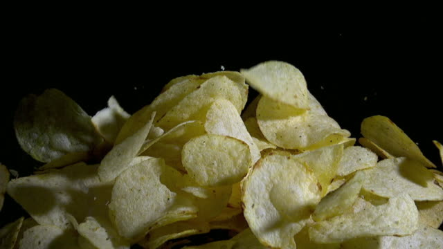 slow motion shot of falling potato chips - crisps stock videos & royalty-free footage