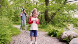 Slow Motion Shot Of Family Hiking Along Path By River In UK Lake District