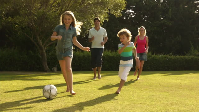slow motion shot of family playing soccer/sotogrande,spain - young family stock videos & royalty-free footage