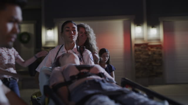 slow motion shot of family watching paramedics put girl on gurney into ambulance at night / lehi, utah, united states - lehi stock videos & royalty-free footage