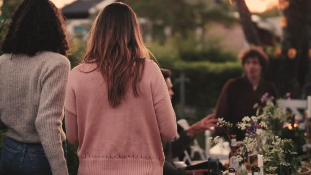 Slow motion shot of female friends arriving in backyard during dinner party