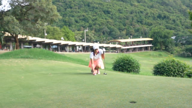 slow motion shot of female golfer putting ball on green - golfer stock videos & royalty-free footage