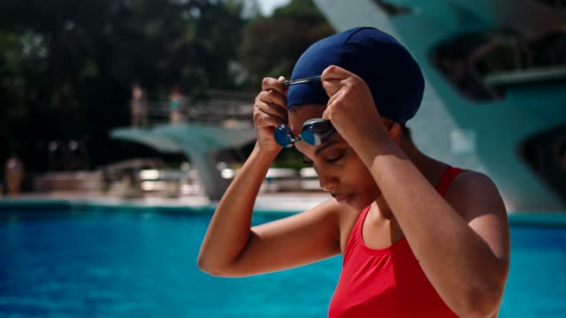 slow motion shot of female swimmer putting on her swim goggles - swimming goggles stock videos & royalty-free footage