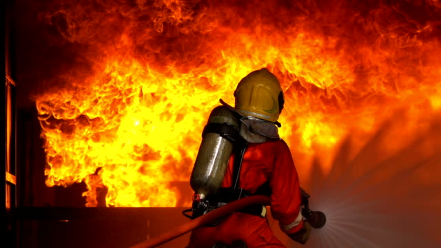 slow motion shot of firemen using fire hose to extinguish a fire inside burning building - fire protection suit stock videos & royalty-free footage