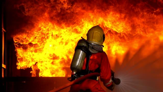 stockvideo's en b-roll-footage met slow motion shot van brandweerlieden met behulp van brand slang te blussen een brand in brandende gebouw - fire hose
