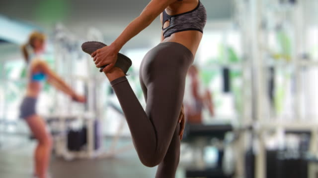 Slow motion shot of fit black female stretching leg muscles at gym