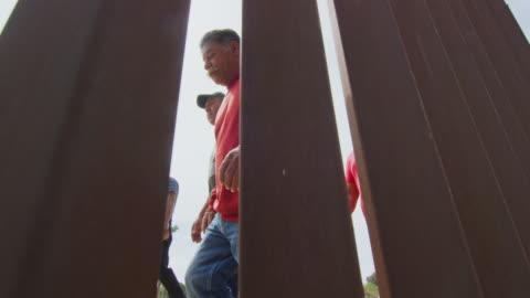 vídeos y material grabado en eventos de stock de disparo a cámara lenta de cinco hombres hispanos y un perro caminando en el lado mexicano de la pared fronteriza de acero-lat de estados unidos / méxico como la cámara películas en el lado de los ee.uu. en un día soleado - cruzar