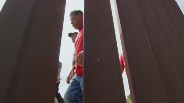 slow motion shot of five hispanic men and a dog walking on the mexican side of the us/mexican steel-slat border wall as the camera films on the us side on a sunny day - geographical border stock videos & royalty-free footage