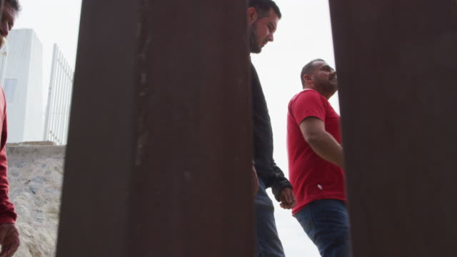 slow motion shot of five hispanic men and a dog walking with a dog on the mexican side of the us/mexican steel-slat border wall as the camera films on the us side on a sunny day - baja california peninsula stock videos & royalty-free footage