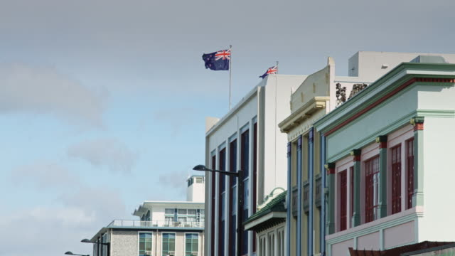 Slow Motion Shot of Flags Flying Over Art Deco Napier Buildings