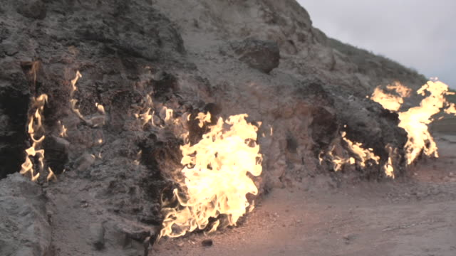 slow motion shot of flames erupting from fissures in the ground at an oil field near baku. - baku video stock e b–roll