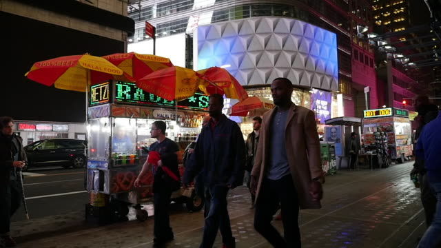 slow motion shot of food vendor and tourists in nyc manhattan times square - concession stand stock videos and b-roll footage