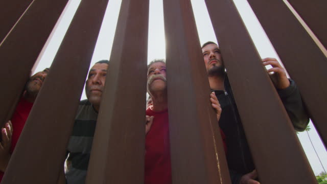slow motion shot of four hispanic men of various ages (on the mexican side) gazing at the united states through the steel-slat border wall between mexico and the united states (shot from the us side) - baja california peninsula stock videos & royalty-free footage