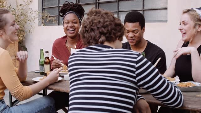 vídeos de stock e filmes b-roll de slow motion shot of friends eating asian takeaway food outdoors - 20 29 anos