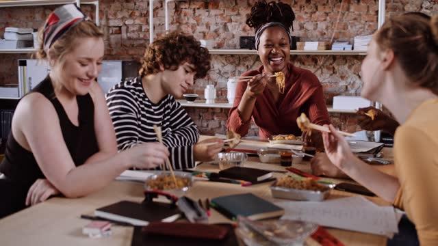 vídeos de stock e filmes b-roll de slow motion shot of friends eating asian takeaway food - 20 29 anos