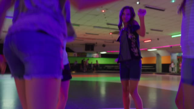 stockvideo's en b-roll-footage met slow motion shot of girls dancing and singing in circle at roller skating rink / orem, utah, united states - driekwartlengte