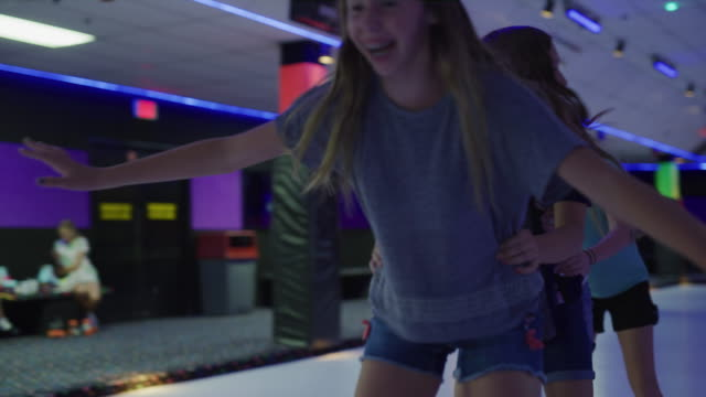 stockvideo's en b-roll-footage met slow motion shot of girls holding waists skating in a row / orem, utah, united states - driekwartlengte