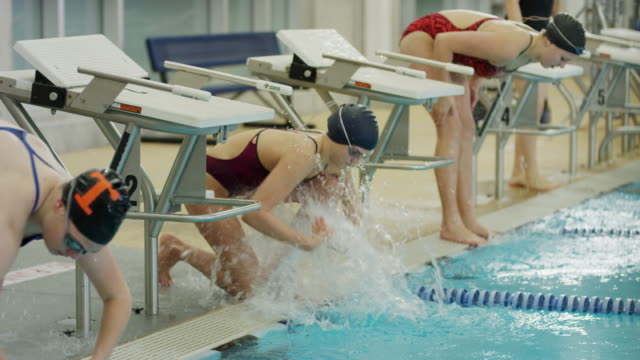 slow motion shot of girls splashing water and warming up before swimming race / provo, utah, united states - warming up stock videos and b-roll footage