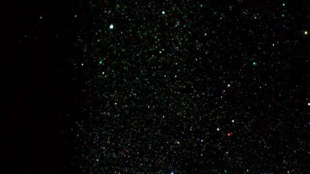 slow motion shot of glitter falling in front of a black background. - glittering stock videos & royalty-free footage