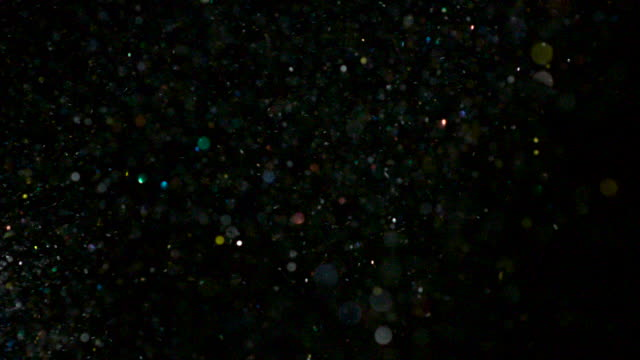 Slow motion shot of glitter falling in front of a black background.