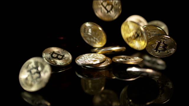 slow motion shot of gold bitcoins falling and bouncing on a reflective black surface - currency symbol stock videos & royalty-free footage