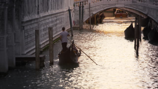 Slow motion shot of gondolier navigating his gondola toward a busy canal bridge in Venice, Italy.