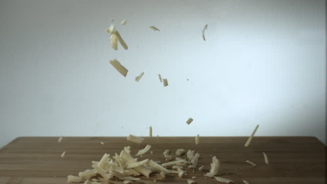 Slow motion shot of grated cheese falling onto a wooden block.