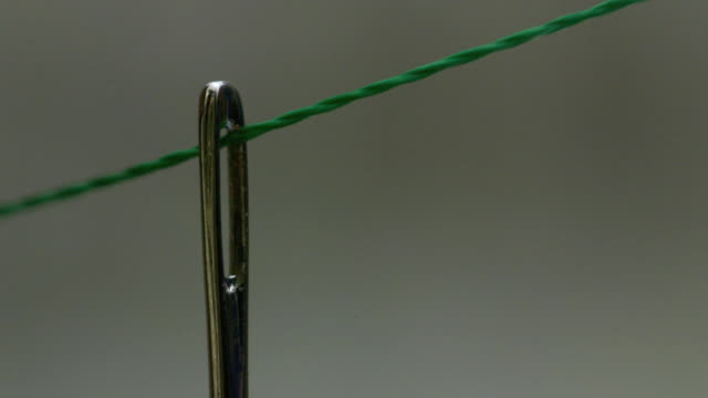slow motion shot of green thread being pulled through the eye of a needle. - sewing stock videos & royalty-free footage