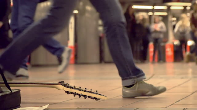 vídeos de stock e filmes b-roll de slow motion shot of guitar and people walking at ny subway station - artista
