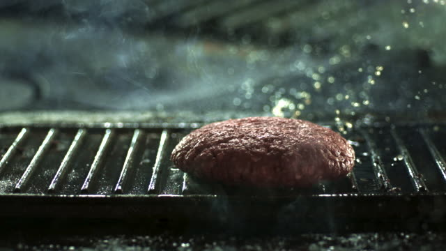 slow motion shot of hamburger being dropped onto a hot griddle. - 肉点の映像素材/bロール