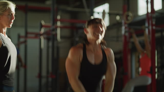 slow motion shot of instructor encouraging woman lifting kettle bell in gymnasium / lehi, utah, united states - lehi stock videos & royalty-free footage