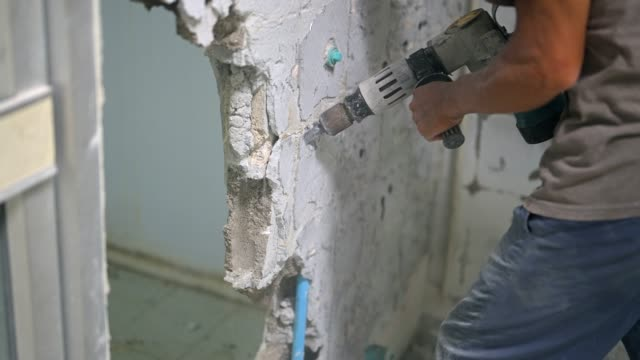 slow motion shot of jackhammer drilling into a wall and white tiles - tile stock videos & royalty-free footage