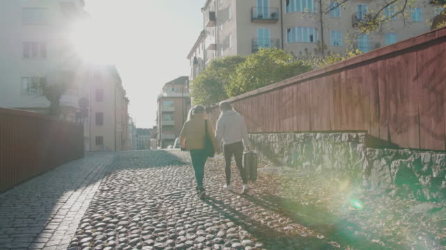 slow motion shot of lesbian couple walking on cobbled street in city during vacation - stockholm stock-videos und b-roll-filmmaterial