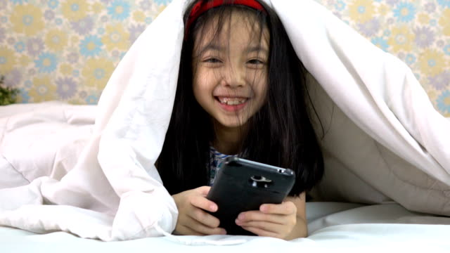 slow motion shot of little girl using smartphone under the blanket - duvet stock videos & royalty-free footage