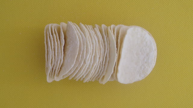 Slow Motion shot of macro stack row of potato chips on yellow background