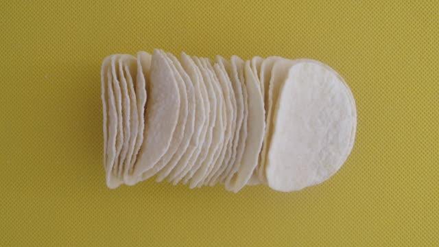 黄色の背景にポテトチップスのマクロスタック行のスローモーションショット - 塩味スナック点の映像素材/bロール