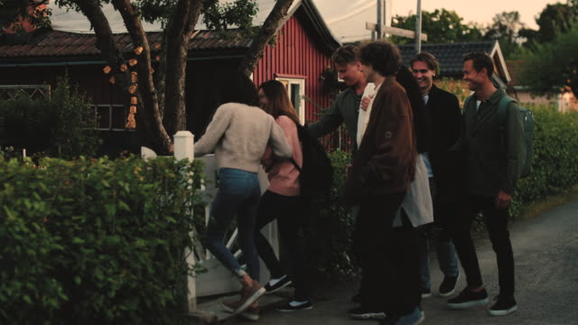 Slow motion shot of male and female friends arriving at backyard for social gathering
