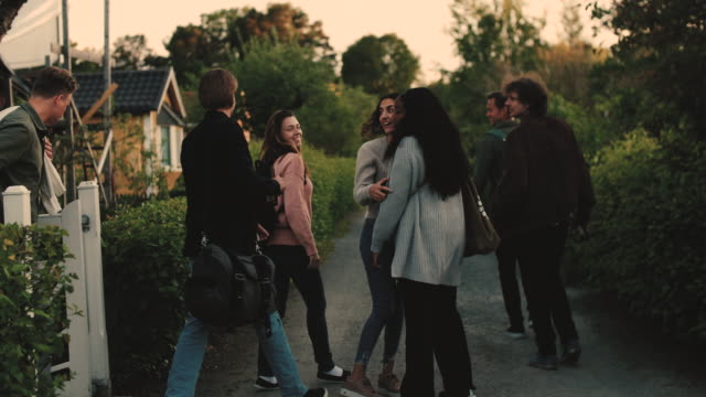 Slow motion shot of male and female friends leaving from yard after social gathering