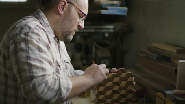 slow motion shot of man cleaning wood with cube pattern in workshop / provo, utah, united states - provo stock videos & royalty-free footage