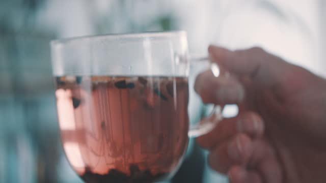 vídeos de stock e filmes b-roll de slow motion shot of man holding tea cup with fruit tea - one mid adult man only